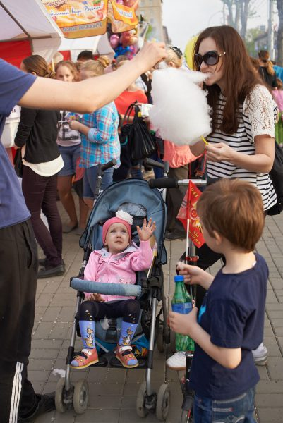 Family is eating cotton candy during street festivities in honor of the Victory Day in Novosibirsk on May 9, 2015